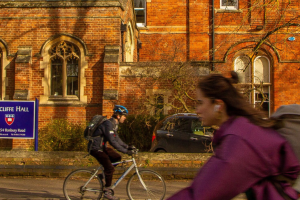 Photo of someone cycling in front of Wycliffe Hall